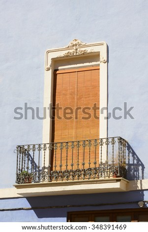 Wrought iron balcony with wooden shuttered door on a blue painted wall in Valencia, Spain - stock photo