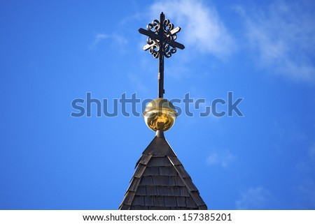 Wrought Iron Cross on Blue Sky / Wooden roof of church with wrought iron cross against the blue sky - Sanctuary of Monte Lussari, Friuli Italy - stock photo