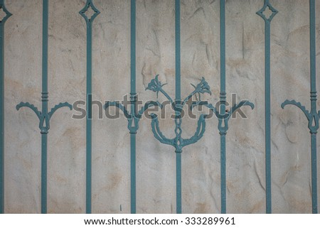 Wrought iron decorative fencing with vintage stucco background for use as an advertising backdrop. - stock photo