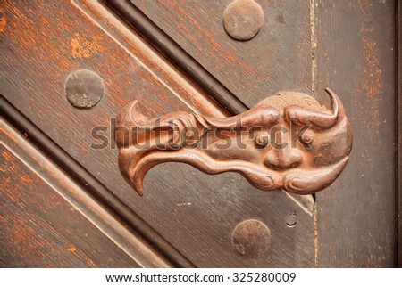 Wrought iron door handle with a mysterious person face - stock photo