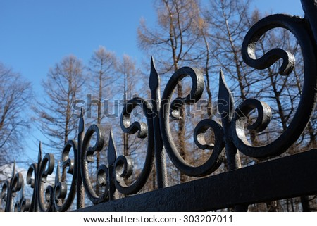 wrought iron fence against the sky and trees - stock photo