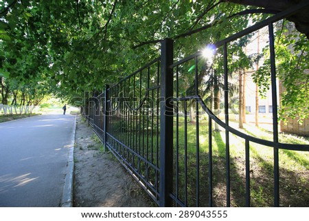 wrought-iron fence in a park - stock photo