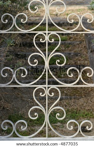 Wrought Iron Gate - Decorative gate opens on stone stairs leading to an abandoned French seaside villa. - stock photo