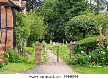 Wrought Iron Gate to an English Churchyard and Cemetery with cottage and flower filled garden - stock photo
