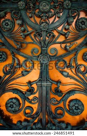 Wrought-iron gates on a yellow background - stock photo