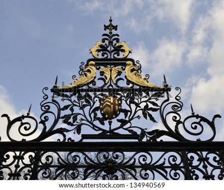 Wrought iron gateway and crest at Clare College, Cambridge - stock photo