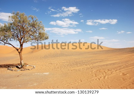 Wrought iron table and chairs on the top of sand dune of Erg Chebbi in the Sahara Desert, Morocco - stock photo