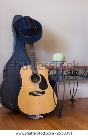 Wrought iron table, modern planter, old wood floors and textured walls with guitar and guitar case. - stock photo