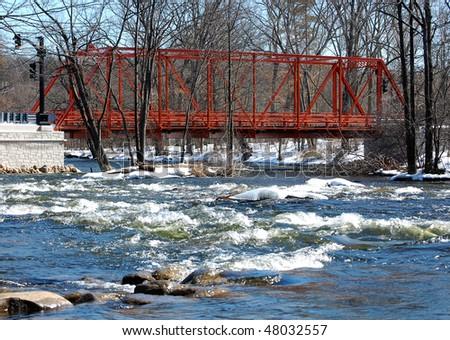 Wrought iron truss bridge, river view, winter scene - stock photo