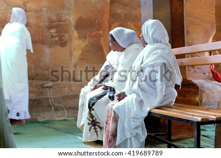 WUKRO, ETHIOPIA-MARCH 29: Orthodox christian devotees attend religious services dressed in habesha kemis and netela white clothes on March 29, 2013 in Wukro Chirkos rock-hewn church. Tigray region.