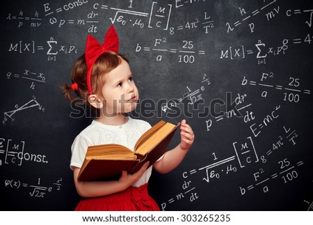 wunderkind little girl schoolgirl with a book from the blackboard with physical formulas - stock photo