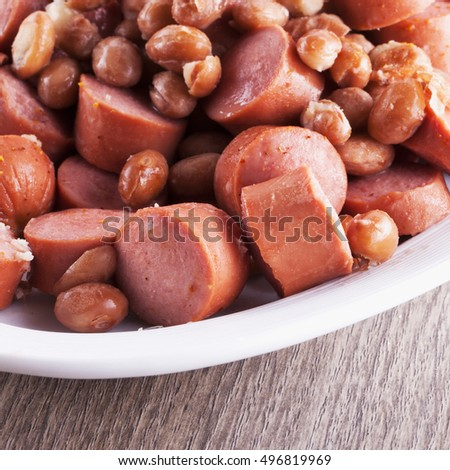 Wurstel and beans in white plate, horizontal image