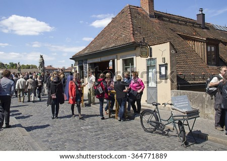 Wurzburg, Germany - May 4, 2014: People drink wine at the cafe in the old custom house on the Old Main Bridge in Wurzburg, Germany on May 4, 2014 - stock photo