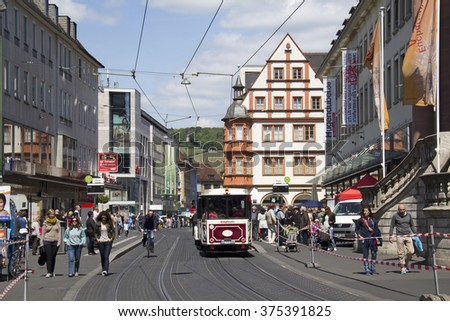 Wurzburg, Germany - May 4, 2014: Red tram and people on foot and on bicycle in a street in central Wurzburg, Germany on May 4, 2014 - stock photo