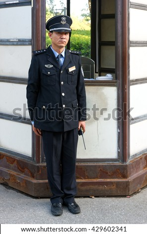 WUXI, CHINA - April 18, 2016: Chinese security guard at his post. China has 4.5 million security guards and about 3,700 security service companies. - stock photo