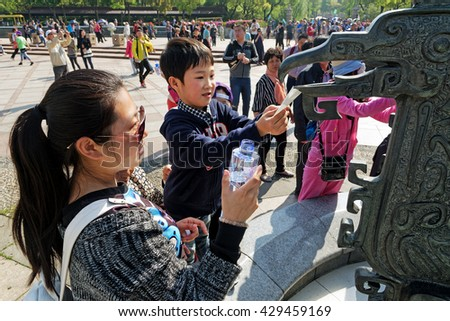 WUXI, CHINA - April 18, 2016: Mother and son collecting sacred water from the Ling Shan Buddhaâ?? fountain in Wuxi, China - stock photo