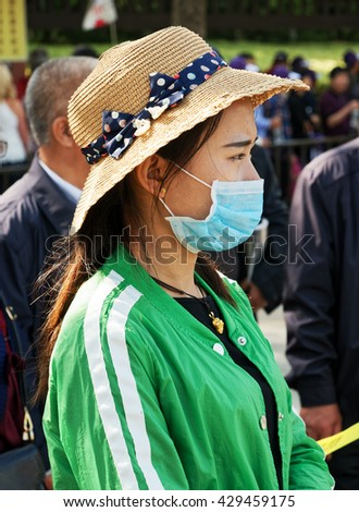 WUXI, CHINA - April 18, 2016: Young Chinese woman wearing a mask for air pollution. In China the air pollution is a severe problem. - stock photo