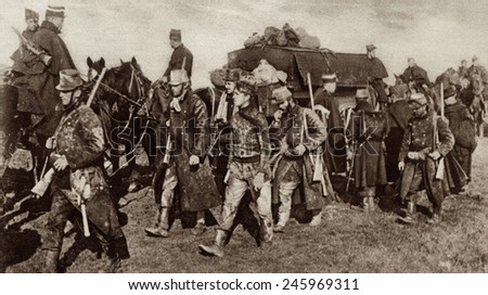 WWI. Belgian troops, weary and mud-covered from fighting in the trenches moving forward to take up a new position near Veurne. 1914. - stock photo