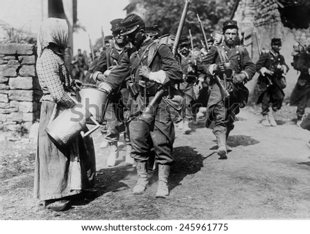WWI. French troops on the march, and during the Battle of the Marne. A village women supplies them with drinking water. Ca. September 6-12, 1914. - stock photo