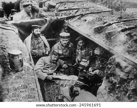 WWI. German soldiers smoking, reading, and writing in their trench. In the background one soldier maintains a battle position. Western Front, ca. 1914-15. - stock photo
