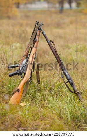 WWII Red soviet Army rifles in piramide and one captured german Submachine Gun - stock photo