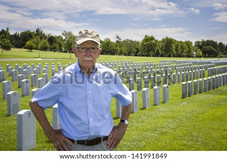 WWII veteran among the headstones at a military cemetery - stock photo