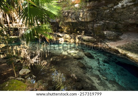 X-Batun Cenote - natural lagoon with transparent turquoise water surrounded by rocks and tropical vegetation - stock photo