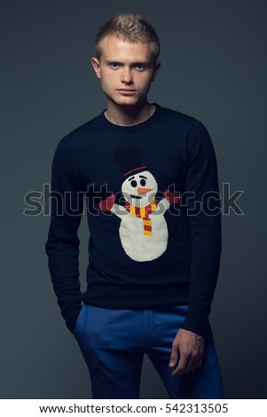 X-mas outfit concept. Portrait of blue-eyed young man with short blond hair wearing blue sweater with Frosty, posing over dark gray background. Studio shot