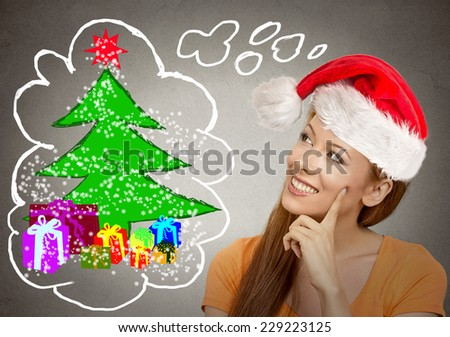 x-mas, winter, happiness concept smiling woman in red santa helper hat looking at christmas tree on grey wall background. Positive emotion face expression perception vision - stock photo