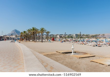 XABIA, SPAIN - SEPTEMBER 7, 2016:Sunbathers on beach-loungers enjoy hot day on beautiful Mediterranean beach on Costa Blanca, September 7, 2016, Xabia   Spain