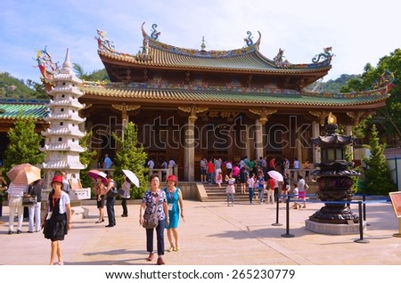 XIAMEN, CHINA, OCTOBER 22, 2013: people are walking through grounds of the most famous buddhist temple in chinese city xiamen - nan putuo - stock photo