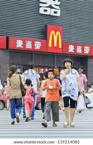 XIANG YANG-CHINA-JULY 3: Mom and her son in front of McDonald on July 3, 2012 in Xiang Yang. It took McDonald 19 years to reach 1,000 restaurants in China. It plans to have 2,000 by 2013. - stock photo