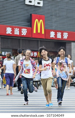 XIANG YANG-CHINA-JULY 3, 2012. Teenagers in front of McDonald's on July 3, 2012 in Xiang Yang. It took McDonald's 19 years to reach 1,000 restaurants in China. It plans to raise it to 2,000 by 2013. - stock photo