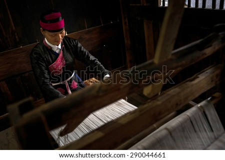 XIAPU, CHINA - JUNE 5, 2015: An unidentified lady wearing traditional costume weaves cloth from cotton strands using a traditional wooden weaving machine of several hundred years old.  - stock photo