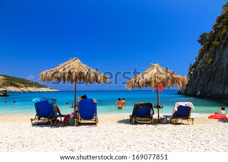 XIGIA, GREECE - CIRCA JULY 2013: People are relaxing under a straw parasol on the beach at Xigia on the island of Zakynthos in July 2013