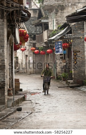 XINGPING, CHINA - MAY 20: A lone cyclist on the rustic street in the thousand year old Xingping town.  May 20, 2010 in Xingping, China.