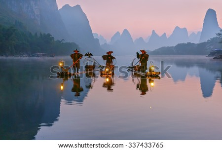 XINGPING, CHINA - OCTOBER 22, 2014: Cormorant fishermans stands on the ancient bamboo boat with a lighted lamps and cormorants in the sunrise - The Li River, Xingping, China - stock photo