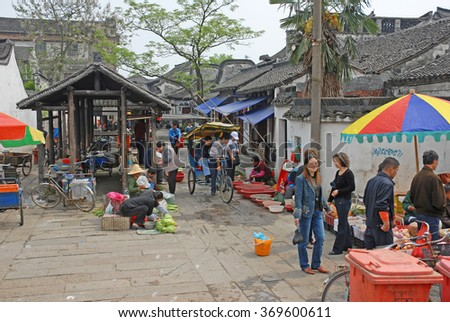 XITANG, SHANGHAI-APRIL 24, 2007: locals and tourists at the village central market. Xitang water village is Shanghai tourist attraction with more than 1000000 visitors year. - stock photo