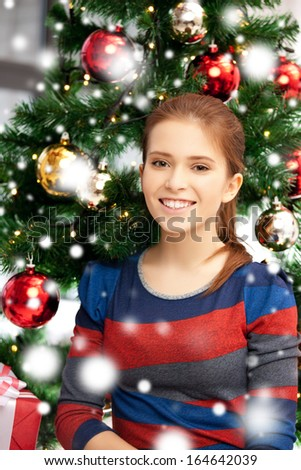 xmas, christmas, winter, holidays and happiness concept - happy woman with gift box and christmas tree - stock photo