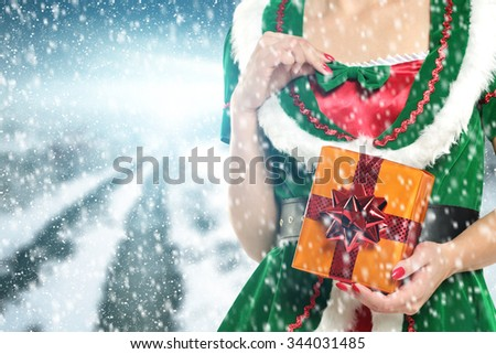xmas elf in green dress and box of golden color  - stock photo