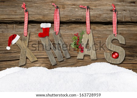 xmas letters with snow on wooden background