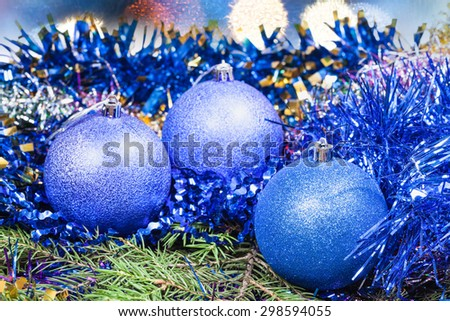 Xmas still life - blue balls, tinsel at green tree with blurred Christmas lights background - stock photo