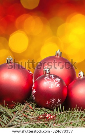 Xmas still life - red balls at green tree with blurred yellow, red, brown Christmas lights bokeh background