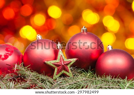 Xmas still life - red baubles, star, green tree with blurred yellow red and brown Christmas lights background - stock photo