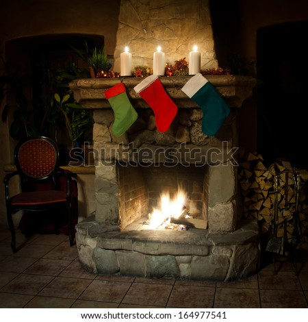 xmas stockings on chimney place background. real fire. vintage interior (front view) - stock photo