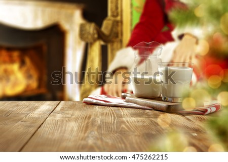 xmas time photo of wooden table with milk and fireplace