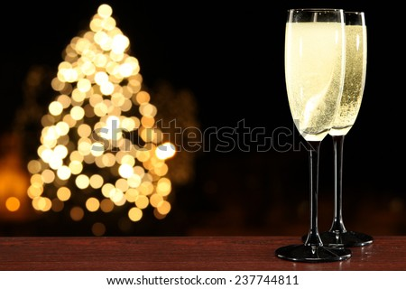xmas tree and champagne in two dark glasses  - stock photo