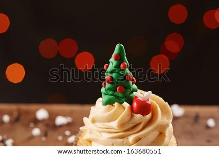 Xmas tree cupcake on white snow flakes Christmas background - stock photo