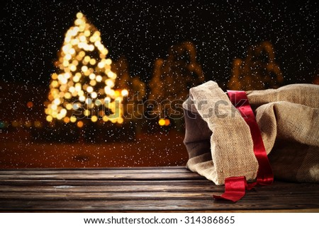 xmas tree on street in city background with ribbon and sack  - stock photo
