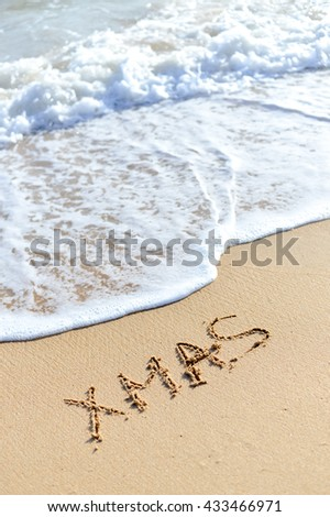 Xmas word sign on tropical beach background - stock photo